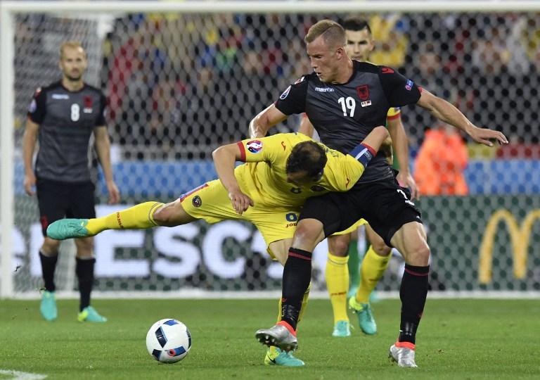 Căpitanul României, Vlad Chiricheș, în duel cu atacantul albanez Bekim Balaj, în timpul partidei disputate la Lyon, pe 19 iunie, în Grupa A a EURO 2016 / AFP PHOTO / PHILIPPE DESMAZES