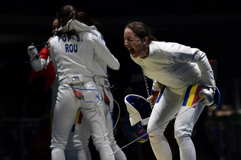 Romania's Ana Maria Popescu (R) reacts after winning the women's team epee quarter-final bout between US and Romania as part of the fencing event of the Rio 2016 Olympic Games, on August 11, 2016, at the Carioca Arena 3, in Rio de Janeiro. / AFP PHOTO / Fabrice COFFRINI