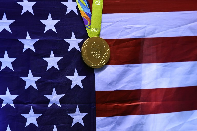 A gold medal is seen on a US flag during a swimming event at the Rio 2016 Olympic Games at the Olympic Aquatics Stadium in Rio de Janeiro on August 11, 2016.   / AFP PHOTO / GABRIEL BOUYS