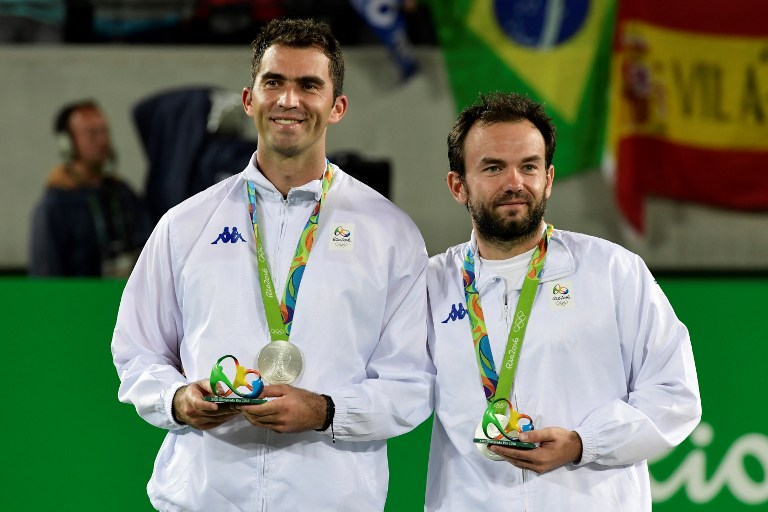 Silver medallists Romania's Florin Mergea (R) and Romania's Horia Tecau pose on the podium of the men's doubles final tennis match at the Olympic Tennis Centre of the Rio 2016 Olympic Games in Rio de Janeiro on August 12, 2016. / AFP PHOTO / JAVIER SORIANO