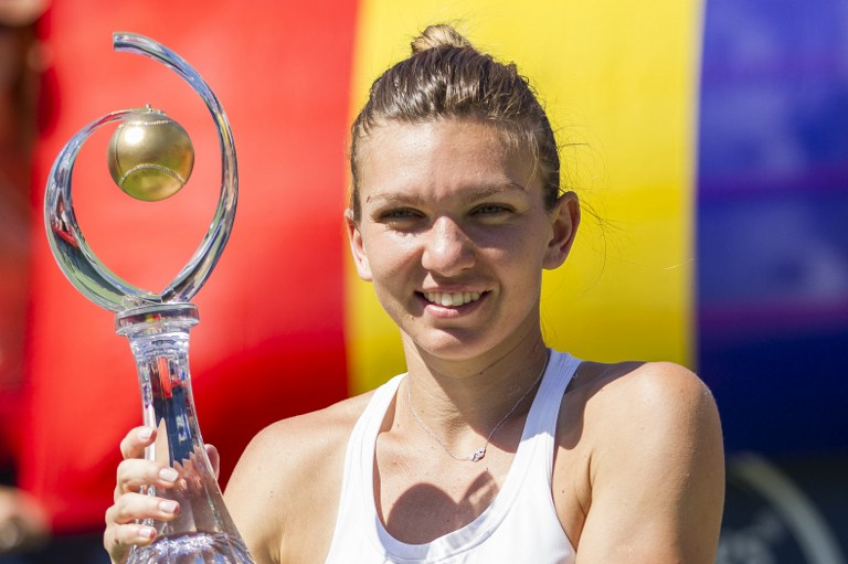 Simona Halep of Romania hoists the Rogers Cup after defeating  Madison Keys of the United States in the final at Uniprix Stadium in Montreal, Quebec, July 31, 2016. Simona Halep beat a mistake-prone Madison Keys 7-6 (7/2), 6-3 on July 31 to win the WTA Montreal hardcourt tournament and claim her 14th career singles crown. / AFP PHOTO / Geoff Robins