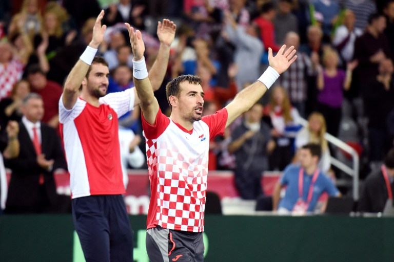 Croatia's tennis players Ivan Dodig (C) and Marin Cilic (rear L) celebrate after winning the Davis Cup World Group final doubles match between Croatia and Argentina at the Arena hall in Zagreb, on November 26, 2016. / AFP PHOTO / STRINGER