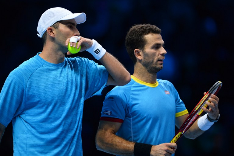 Netherland's Jean-Julien Rojer (R) and Romania's Horia Tecau celebrate after beating France's Nicolas Mahut and Pierre-Hugues Herbert in a men's doubles group stage match on day six of the ATP World Tour Finals tennis tournament in London on November 20, 2015.  AFP PHOTO / GLYN KIRK / AFP PHOTO / GLYN KIRK