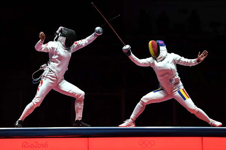 China's Hao Jialu (L) competes against Romania's Loredana Dinu during the women's team epee gold medal bout between China and Romania as part of the fencing event of the Rio 2016 Olympic Games, on August 11, 2016, at the Carioca Arena 3, in Rio de Janeiro. / AFP PHOTO / Kirill KUDRYAVTSEV