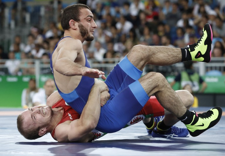 Bulgaria's Vladimir Vladimirov Dubov (red) wrestles with Romania's Ivan Guidea in their men's 57kg freestyle round of 16 match on August 19, 2016, during the wrestling event of the Rio 2016 Olympic Games at the Carioca Arena 2 in Rio de Janeiro. / AFP PHOTO / Jack GUEZ