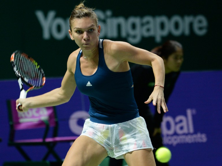 Romania's Simona Halep hits a return against Madison Keys of the US during their first round women's singles match at the WTA Finals tennis tournament in Singapore on October 23, 2016. / AFP PHOTO / ROSLAN RAHMAN