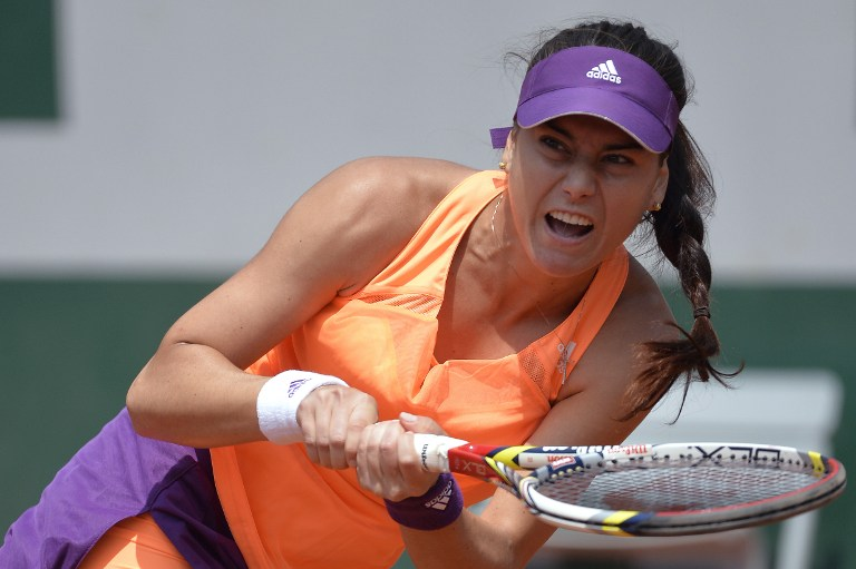 Romania's Sorana Cirstea returns the ball to Serbia's Jelena Jankovic during their French tennis Open third round match at the Roland Garros stadium in Paris on May 31, 2014.  AFP PHOTO / MIGUEL MEDINA / AFP PHOTO / MIGUEL MEDINA