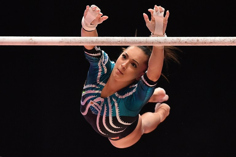 Romanian gymnast Larisa Andreea Iordache competes on the uneven bars during the Women's All-Around final on the seventh day of the 2015 World Gymnastics Championship in Glasgow, Scotland, on October 29, 2015. Gymnasts can secure qualification for the 2016 Rio Games at the championships which are being staged at the Hydro Arena.  AFP PHOTO / BEN STANSALL / AFP PHOTO / BEN STANSALL