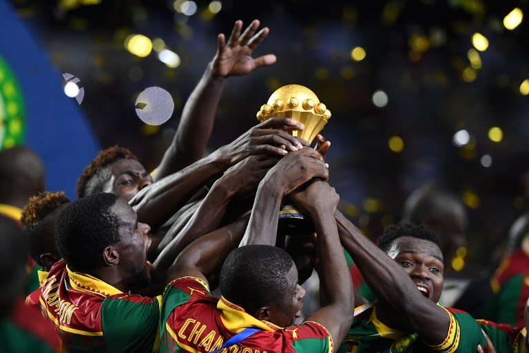 Cameroon team players hold up the winner's trophy as they celebrate beating Egypt 2-1 to win the 2017 Africa Cup of Nations final football match between Egypt and Cameroon at the Stade de l'Amitie Sino-Gabonaise in Libreville on February 5, 2017. / AFP PHOTO / GABRIEL BOUYS