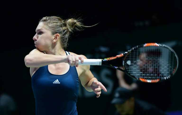 Romania's Simona Halep hirts a return against Madison Keys of the US during their singles match at the WTA Finals tennis tournament in Singapore on October 23, 2016. / AFP PHOTO / ROSLAN RAHMAN
