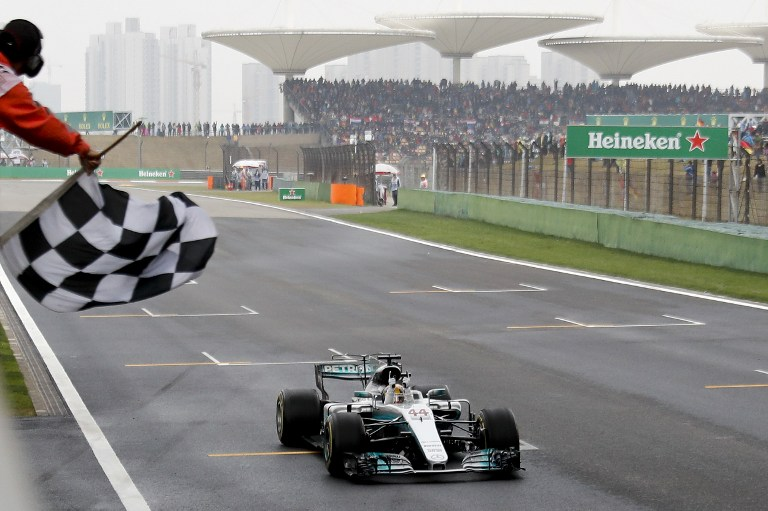 Mercedes' British driver Lewis Hamilton drives his car past the chequered flag to win the Formula One Chinese Grand Prix in Shanghai on April 9, 2017. / AFP PHOTO / POOL / Andy WONG